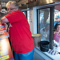 """Wayne Robertson, left, and Brenda Robertson work quickly to resupply cones to hand out to students at the University of New Mexico-Gallup campus. The Robertson's brought their """"Tasty Shack"""" to the  campus located in Gallup, New Mexico."""
