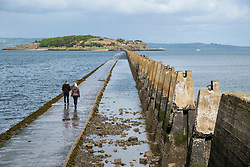 Couple walking on tidal causeway towards Cramond Island in Edinburgh, Scotland, UK. Concrete structures are wartime anti-submarine defences.