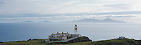 Neist Point lighthouse and view across waters of the Little Minch to islands of the Outer Hebrides, Isle of Skye, Scotland