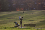 A father holds up a baby before placing it back in the childs buggy during a loving moment on 18th November 2016, in Brockwell Park, Herne Hill, Lambeth SE24 south London, England.