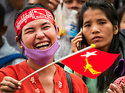 09 NOVEMBER 2015 - YANGON, MYANMAR: A woman laughs and waves a NLD flag Monday. Thousands of National League for Democracy (NLD) supporters gathered at NLD headquarters on Shwegondaing Road in central Yangon to celebrate their apparent landslide victory in Myanmar's national elections that took place Sunday. The announcement of official results was delayed repeatedly Monday, but early reports are that the NLD did very well against the incumbent USDP.     PHOTO BY JACK KURTZ