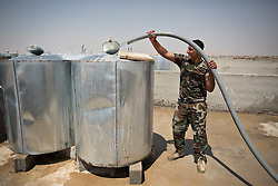© Licensed to London News Pictures. Hamdaniyah, Iraq. 26/07/2014. A Kurdish Zeravani soldier fills water tanks on the roof of a partially finished house in Hamdaniyah, Iraq, where Christian refugees who recently fled from Mosul now live.<br /> <br /> <br /> Having taken over Mosul Iraq's second largest city in June 2014, fighter of the Islamic State (formerly known as ISIS) have systematically expelled the cities Christian population. Despite having been present in the city for more than 1600 years, Christians in the city were given just days to either convert to Islam, pay a tax for being Christian or leave; many of those that left were also robbed at gunpoint as they passed through Islamic State checkpoints.. Photo credit : Matt Cetti-Roberts/LNP