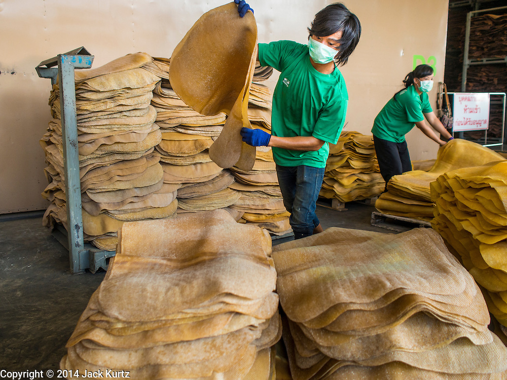 """15 DECEMBER 2014 - KLAENG, RAYONG, THAILAND: TA worker stacks rubber sheets at Supark, a rubber processing plant in Klaeng, Thailand. Thailand is the second leading rubber exporter in the world. In the last two years, the price paid to rubber farmers has plunged from approximately 190 Baht per kilo (about $6.10 US) to 45 Baht per kilo (about $1.20 US). It costs about 65 Baht per kilo to produce rubber ($2.05 US). Prices have plunged 5 percent since September, when rubber was about 52Baht per kilo. Some rubber farmers have taken jobs in the construction trade or in Bangkok to provide for their families during the slump. The Thai government recently announced a """"Rubber Fund"""" to assist small farm owners but said prices won't rebound until production is cut and world demand for rubber picks up.      PHOTO BY JACK KURTZ"""