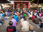 "09 AUGUST 2014 - BANGKOK, THAILAND:     People wait for free meals at the Ruby Goddess Shrine in the Dusit section of Bangkok. The seventh month of the Chinese Lunar calendar is called ""Ghost Month"" during which ghosts and spirits, including those of the deceased ancestors, come out from the lower realm. It is common for Chinese people to make merit during the month by burning ""hell money"" and presenting food to the ghosts. At Chinese temples in Thailand, it is also customary to give food to the poorer people in the community.   PHOTO BY JACK KURTZ"