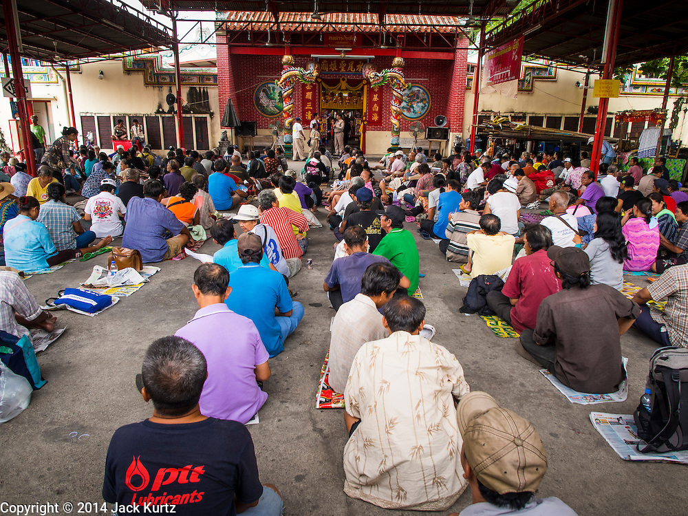 """09 AUGUST 2014 - BANGKOK, THAILAND:     People wait for free meals at the Ruby Goddess Shrine in the Dusit section of Bangkok. The seventh month of the Chinese Lunar calendar is called """"Ghost Month"""" during which ghosts and spirits, including those of the deceased ancestors, come out from the lower realm. It is common for Chinese people to make merit during the month by burning """"hell money"""" and presenting food to the ghosts. At Chinese temples in Thailand, it is also customary to give food to the poorer people in the community.   PHOTO BY JACK KURTZ"""