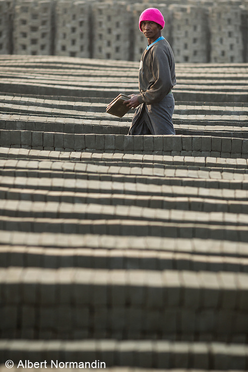 Man carries bricks out to dry at factory, Sittwe