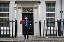 © Licensed to London News Pictures. 22/11/2017. London, UK. Chancellor of the Exchequer Philip Hammond holds up his red ministerial box for photographers as he leaves Number 11 Downing Street for Parliament on budget day. Photo credit: Peter Macdiarmid/LNP
