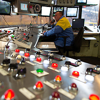 Tata Steel , Corby - Electrical control panel with lights and steel worker operating the plant machinery