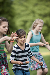Group of girls competing in an egg-and-spoon race in a park, Munich, Bavaria, Germany