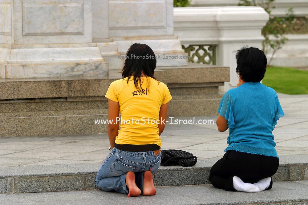 women Praying at an outside Buddhist shrine Thailand, Bangkok,