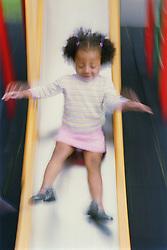 Young girl sliding down playground slide,