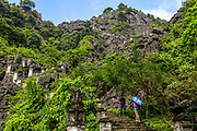 A man and woman with an umbrella on the stone stairway up from Mau Cave, Tam coc, Vietnam. RAW to Jpg