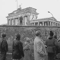 Grenzsoldaten der DDR sind auf der Mauer am Brandenburger Tor postiert. Blickrichtung in den Westen, ihre Gesichter versteinert.