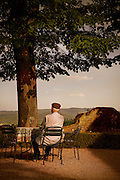 An elderly man sits at a table looking out at the countryside in a town in Italy