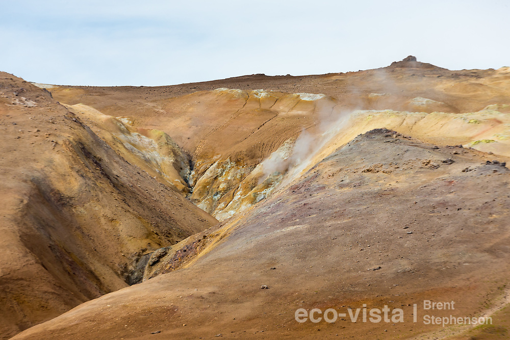 Sulphur enriched soil and colours on the slopes of a hillside, with steam billowing from on of the active steam-vents. Namafjall Geothermal Area, Myvatn, Iceland. July.