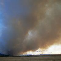 Gallatin Valley, near Bozeman, Montana. A forest fire burns near farms below Gallatin Mountains.