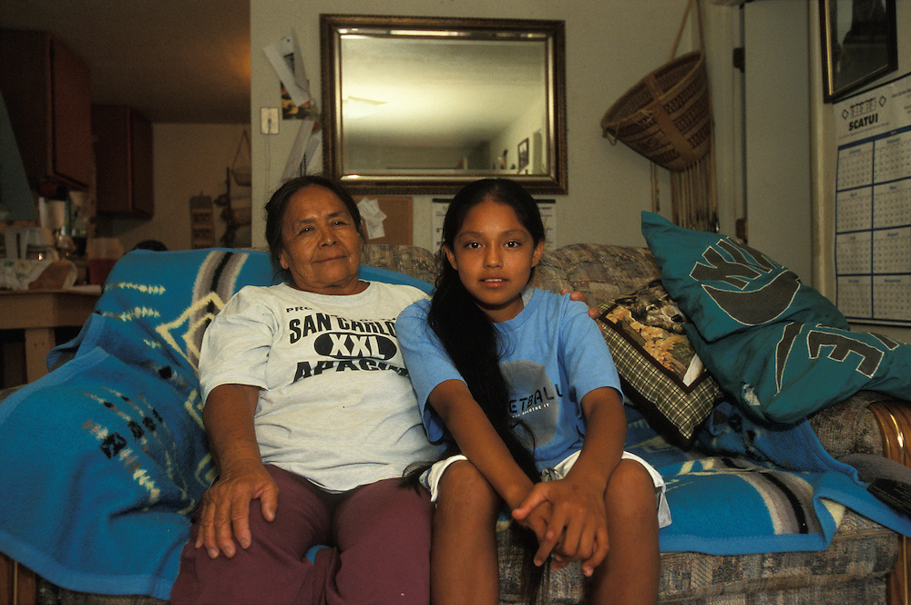 An Apache girl sits together with her grandmother in their livingroom on the San Carlos Apache Indian Reservation in Arizona, USA. June 2004.