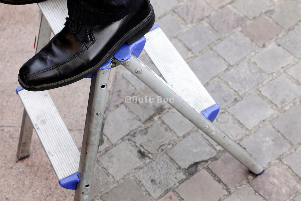 businessman with shiny polished shoes on a little stepladder