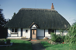 Black and white cottage with thatched roof,