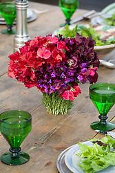 Arrangement of sweet peas in rosemary covered vase