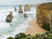 """Twelve Apostles Marine National Park protects several collections of miocene limestone sea stacks in the Indian Ocean (or Southern Ocean according to Australian geographers) offshore of Port Campbell National Park, along the Great Ocean Road, Victoria, Australia. Known as the """"Sow and Piglets"""" until 1922, the pictured set of sea stacks was renamed to """"The Apostles"""" then to Twelve Apostles for tourism, despite only having nine sea stacks (2004 photo). Eight stacks remained after the one at left collapsed in 2005. The Great Ocean Road (B100) is a 243-km road along the southeast coast of Australia between Torquay and Warrnambool, in the state of Victoria. Dedicated to casualties of World War I, the Great Ocean Road was built by returned soldiers between 1919 and 1932 and is the world's largest war memorial."""