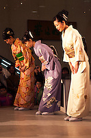 Bowing at the Kimono Show, Nishijin Textiles; Kimono are made of silk and normally very expensive though there is now a thriving market in second hand kimono. Nowadays they are worn at formal or traditional occasions such as funerals, weddings or tea ceremonies. Kimono differ in style and color depending on the occasion on which it is worn and the age and marital status of the person wearing it. To put on a kimono needs some practice. Especially tying the belt (obi) alone is difficult so that many people require assistance. Wearing a kimono properly includes proper hair style, traditional shoes, socks, underwear, and a small handbag for women.