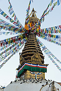 """Kathesimbhu means """"Kathmandu Swayambhu"""". This 17th century stupa (bell-shaped Buddhist monument) in Kathmandu, Nepal, is a smaller version of the more famous """"Monkey Temple"""" at Swayambhu. A walk around the Kathesimbhu stupa promises the old and lame the same blessings as a pilgrimage to Swayambhunath's hill. Buddha Eyes gaze from one side of Swayambhunath, the """"Monkey Temple"""". On most every stupa (Buddhist shrine) in Nepal, giant Buddha Eyes (or Wisdom Eyes) stare from four sides of the upper cube. These four directions symbolize the omniscience (all-seeing) of a Buddha. The third eye (above and between the other two eyes) also symbolizes the all-seeing wisdom of the Buddha. The curled symbol (shaped like a question mark) in place of a nose is the Nepali character for the number 1, which symbolizes unity of all things. The upper part of the spire has 13 gilded disks representing the 13 steps to Buddhist enlightenment, and enlightenment is represented by an upper umbrella."""