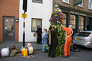 May Day custom of Deptford Jack in the Green, a man encased in a framework entirely covered with greenery, is one of the lesser-known modern revivals by the Blackheath Morris Men of English traditional customs on May 1st 2016 in London, United Kingdom. Preparations out in the street outside the Dog and Bell pub. Fowlers Troop Jack in the Green was revived in the early 1980s. Originally a revival from about 1906, it developed from the 17th Century custom of milkmaids going out on May Day with the utensils of their trade, decorated with garlands of flowers and piled into a pyramid which they carried on their heads. By the mid eighteenth century other groups, notably chimney sweeps, were moving in on the milkmaids territory as they saw May Day as a good opportunity to collect money, so carried a Jack in the Green. Over the last 25 years several popular festivals have grown up around the Jack in the Green tradition. Deptford Jack in the Green is not very widely known although it has been running since the early 1980s.