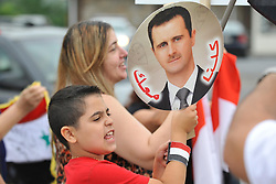 8/28/2013 Allentown, PA A young boy holds a sign supporting Syrian president Bashar as-Assad. Members of the Lehigh Valley Syrian community rally for the second day against the United States' possible involvement in the Syria civil war.