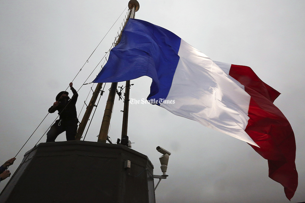 A 35-foot-long French flag, specially made in Tukwila, flies at half-staff atop the Space Needle on Saturday. (Alan Berner / The Seattle Times).
