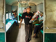 26 OCTOBER 2015 - YANGON, MYANMAR:  A newspaper vendor walks through the Yangon Circular Train. The Yangon Circular Railway is the local commuter rail network that serves the Yangon metropolitan area. Operated by Myanmar Railways, the 45.9-kilometre (28.5mi) 39-station loop system connects satellite towns and suburban areas to the city. The railway has about 200 coaches, runs 20 times daily and sells 100,000 to 150,000 tickets daily. The loop, which takes about three hours to complete, is a popular for tourists to see a cross section of life in Yangon. The trains run from 3:45 am to 10:15 pm daily. The cost of a ticket for a distance of 15 miles is ten kyats (~nine US cents), and for over 15 miles is twenty kyats (~18 US cents).    PHOTO BY JACK KURTZ