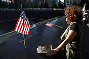 people at the South Pool of the 9/11 memorial to the World Trade Center in New York City