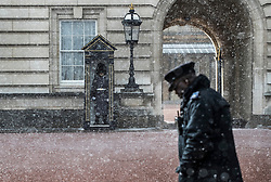 © Licensed to London News Pictures. 26/02/2018. London, UK. A policeman gets caught in a snow shower as he crosses the forecourt at Buckingham Palace as a cold front sweeps in from the east - with heavy snow expected later in parts of the UK. Photo credit: Peter Macdiarmid/LNP