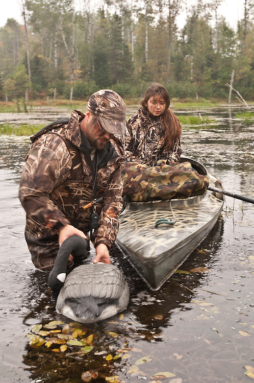 A young female waterfowl hunter and her guide pick up goose decoys.