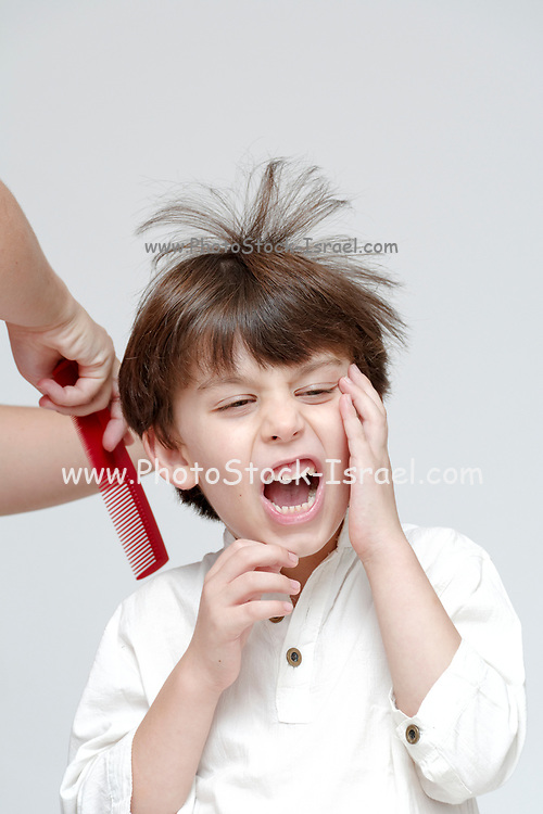 Young boy of six suffers while his hair is combed Model releases