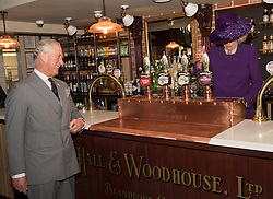 The Duchess of Cornwall pours the Prince of Wales a drink as they officially open the Duchess of Cornwall Inn during a visit to Poundbury, a new urban development on the edge of Dorchester.