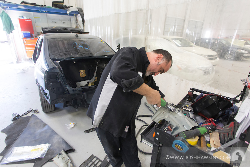 John Kabakoulak putting rubber seal in trunk of car.<br /> <br /> JH_201510021116_MG_6080.CR2<br /> 10/2/2015  --  11:16:49