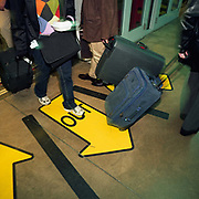 Air passengers exit and enter a transit train at Chicago O'Hare airport, Illinois USA. They pull suitcases behind them as they negotiate the airport terminal transport system that takes them across the sprawling complex of terminals and tunnels. A large central yellow traffic arrow saying OUT is most prominent telling arriving people to keep in the middle, allowing those departing to enter the carriage from the sides. There is a slight blur to the picture showing the hurrying nature of modern air travel, vastly different from the pioneering days of flight for only the socially elite. Picture from the 'Plane Pictures' project, a celebration of aviation aesthetics and flying culture, 100 years after the Wright brothers first 12 seconds/120 feet powered flight at Kitty Hawk,1903.