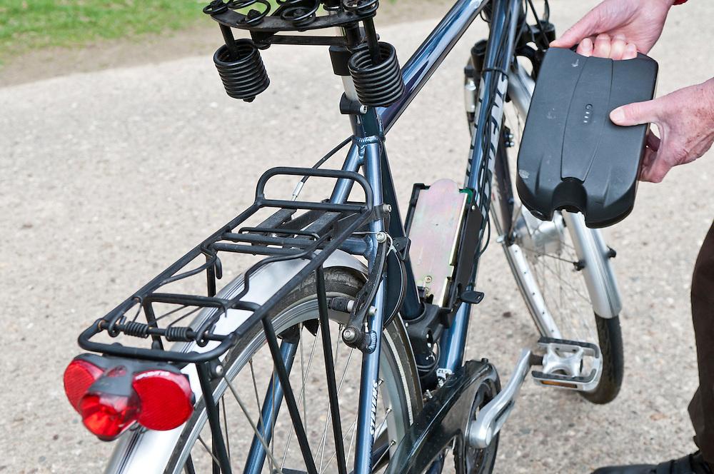Ein Mann im Rentenalter setz den Akku seines Elektrofahrrad ein     a man puts the batterie of an e-bike in place