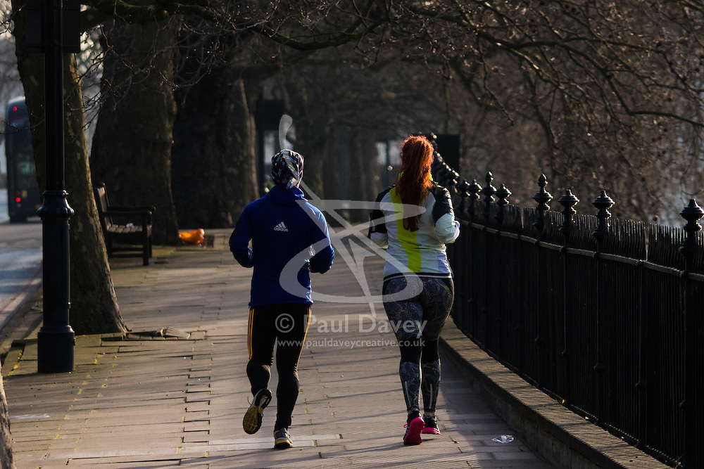 London, February 24th 2016. Runners jog beside the River Thames as the sun rises on a chilly but clear London morning. ///FOR LICENCING CONTACT: paul@pauldaveycreative.co.uk TEL:+44 (0) 7966 016 296 or +44 (0) 20 8969 6875. ©2015 Paul R Davey. All rights reserved.