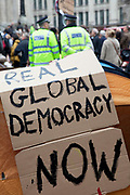 "Real Global Democracy Now sign on a tent set up in the area in front of St Pauls. Occupy London protest at St Pauls, October 16th 2011. Protest spreads from the US with this demonstrations in London and other cities worldwide. The 'Occupy' movement is spreading via social media. After four weeks of focus on the Wall Street protest, the campaign against the global banking industry started in the UK this weekend, with the biggest event aiming to ""occupy"" the London Stock Exchange. The protests have been organised on social media pages that between them have picked up more than 15,000 followers. Campaigners gathered outside  at midday before marching the short distance to Paternoster Square, home of the Stock Exchange and other banks.It is one of a series of events planned around the UK as part of a global day of action, with 800-plus protests promised so far worldwide.Paternoster Square is a private development, giving police more powers to not allow protesters or activists inside."