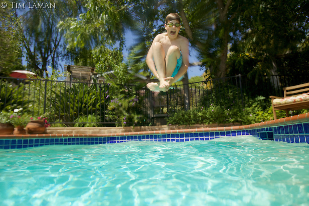 A 13 year-old boy doing a canon ball into the deep end of a pool.