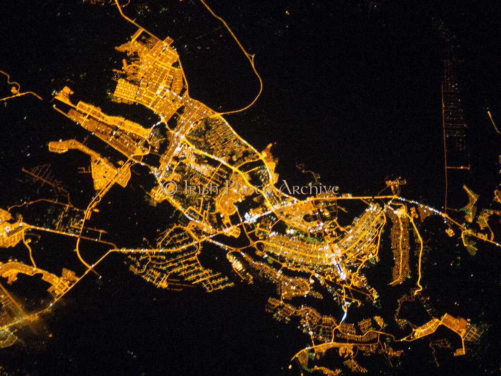 Whether seen at night or during the day, the capital city of Brazil is unmistakable from orbit. Brasília is located on a plateau—the Planalto Central—in the west-central part of the country, and is widely considered to be one of the best examples of 20th century urban planning in the world. One of its most distinctive design features—as seen from above—suggests a bird, butterfly, or airplane traveling along a northwest-southeast direction, and is made dramatically visible by city light patterns (image centre right, between Lake Paranoá and the airport). Following the establishment of Brasília in the early 1960s, informal settlements began to form around the original planned city. Ceilândia was one such settlement. In 1970, Ceilândia was formalized by the government and is now a satellite city of Brasília with its own distinct urban identity.