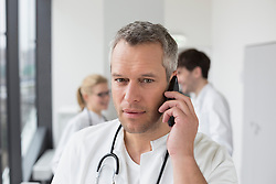 Doctor on phone while colleagues in background