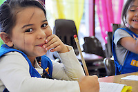 One happy Girl Scout, five year-old Angelina Villegas does her homework at the Alisal Program Center near Closter Park in Salinas. Through the center, these girls have a wealth of safe after-school activities from Monday through Friday from 2:45 to 5:45 PM, with Wednesdays starting at 1:45 PM. Their Monday afternoon consisted of homework help, a healthy meal provided by the district, a mile walk, their weekly visit from the bookmobile, and a science lesson. Tuesdays are devoted to Journey, their incremental path toward higher levels of Scouting, Wednesdays to cooking and arts, Thursdays to folkloric dancing and Journey, with Fridays featuring computer and general fun and games. In anticipation of the upcoming Holiday Parade of Lights, the troop will also be making a hundred colorful arts and crafts pins to be traded with other participating groups.