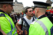 Police get into discussion with a protester they de-masked. Demonstration by unions and other organisations of workers to mark the annual May Day or Labour Day. Groups from all nationalities from around the World, living in London gathered to march to a rally in central London, UK.