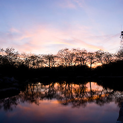 Trees and sunset sky reflections on a pond on Mount Wachusett.  Mount Wachusett State Paek, Massachusetts.