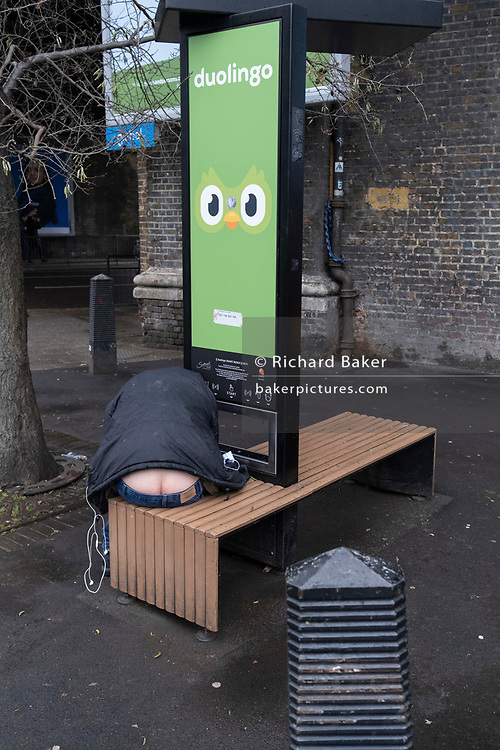 Tge rear of a man is seen between clothing of a man bending down to listen to his phone that is re-charging at a Duolingo Wi-fi Smart Bench at Elephant & Castle in south London, on 20th January 2021, in London, England.