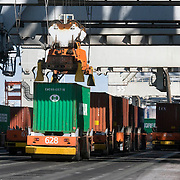 Nederland Zuid-Holland Rotterdam  27-08-2009 20090827 Foto: David Rozing .Serie over logistieke sector.ECT Delta terminal in de haven van Rotterdam. Robotgestuurde wagens vervoeren de containers op de terminal. Onbemande wagens in de rij bij de hijskranen, deze tillen de containers op het zeeschip. .ECT,European Container Terminals, at the Port of Rotterdam. Europe's biggest and most advanced container terminal operator, handling close to three- quarters of all containers passing through the Port of Rotterdam. ECT is a member of the Hutchison Port Holdings group (HPH), the world biggest container stevedore with terminals on every Continent. At the ECT Delta Terminal unmanned, automated guided vehicles  so called AGVs  transport the containers between ship and stack. In the stack, unmanned automated stacking cranes ( ASCs ) ensure that the containers are always stacked in the correct place. Terminal operations are highly automated for discharging and loading large volumes , , zeehaven, zeehavens..Holland, The Netherlands, dutch, Pays Bas, Europe .Foto: David Rozing