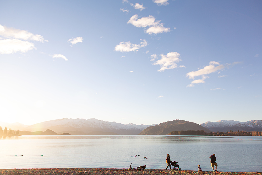 Distant view of a dad skimming stones across Lake Wanaka watched on by the Mum with young children on the shores of Lake Wanaka, South Island NZ.